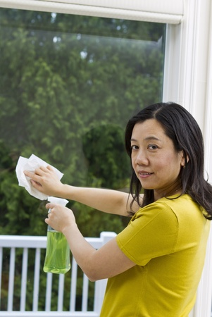 window cleaning: Asian woman cleaning window with spray bottle and paper towel in hand