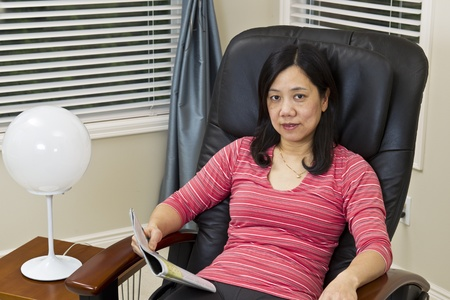 Asian lady reading magazine while relaxing in massage chair at home photo