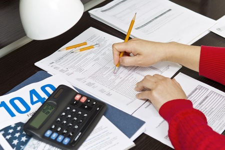 Woman hands with pencil eraser, calculator, lamp, tax forms on desk top photo