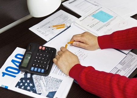 Pencil being snapped in two in front of tax forms with calculator, pencils and lamp on desktop