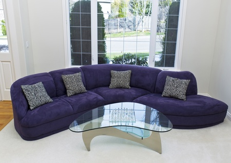 Large family sofa in living room with glass table in front and large window in background  photo