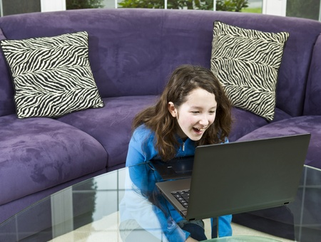 Young girl looking at laptop while laughing with couch in background photo