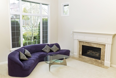 living room sofa: Living room with sofa, glass table, fireplace and carpet floors with large window in background