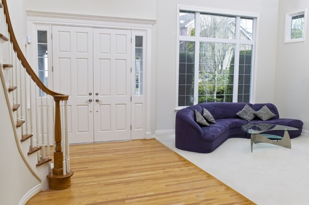 new construction renovation: Living room with sofa, glass table, oak and carpet floors with large window in background