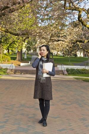 Las mujeres asiáticas de pie en la acera mientras se mantiene blocs de notas del libro de árboles de cerezo y el cielo azul en el fondo Foto de archivo - 12955887