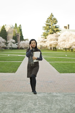 Asian women standing on sidewalk while holding note book pads with cherry trees and blue sky in background photo
