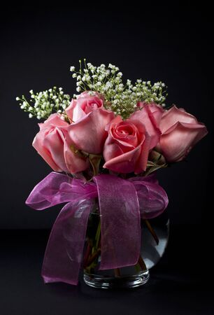 vase: Pink roses with small white flowers in glass vase on dark background Stock Photo