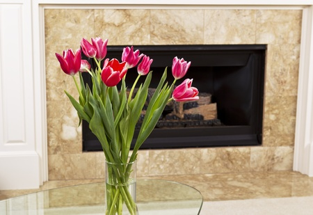 Seasonal flowers on table in front of fire place photo
