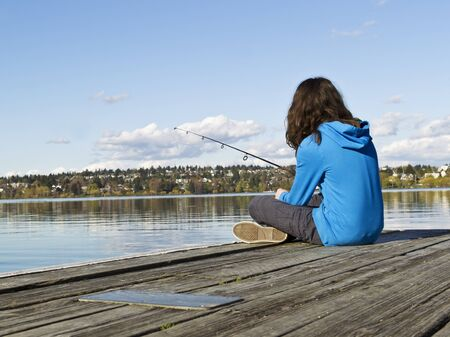 fishing pole: Young girl fishing off dock in Lake Washington during sunny day
