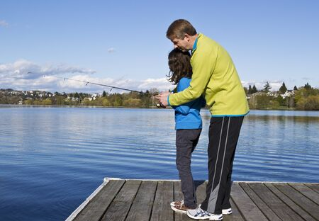 Father teaching daughter how to fish off dock in Lake Washington