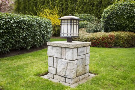 hedging: Asian lantern post in front yard with evergreens in background