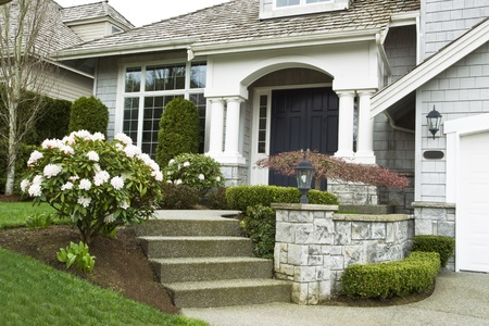 upscale: Entrance to house during springtime with blooming flowers  Stock Photo