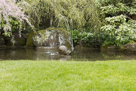 Outdoor water fountain spraying in garden pond with large rock in background Imagens
