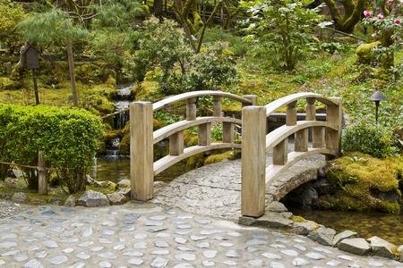 Wooden bridge crossing stream in Japanese Garden Stock Photo
