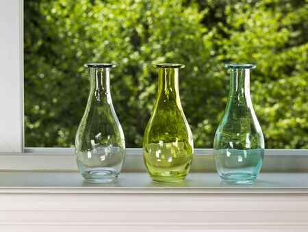 sill: Open window with three vases on sill with green trees in background Stock Photo