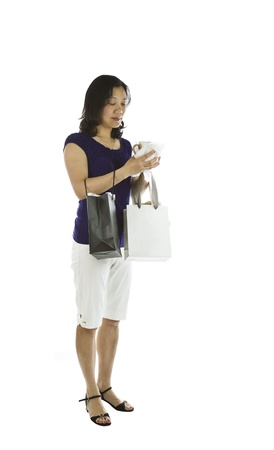 Mature Asian women carry shopping bags with coffee mug in hands on white background Stock Photo - 13701442