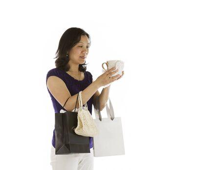 Mature asian women inspecting new coffee mug on white background Stock Photo - 13701445