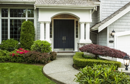 Front Door to home surrounded by seasonal plants and part yard and sidewalk in forefront  Stock Photo