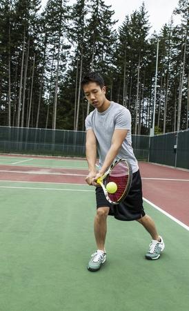 backhand: Hombre joven golpeando de rev�s dos manos en la masa en la cancha de tenis al aire libre con �rboles en el fondo