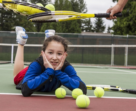 children at play: Young girl being given acceptance into tennis group with rackets over her head