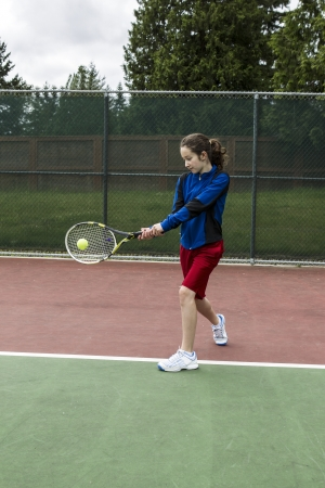 children at play: Young girl using a two handed backhand for lefthand tennis Player  Stock Photo