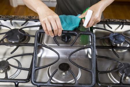 estufa: Las manos levantar la rejilla delantera de la gama de cocina de la parte superior con una botella de spray en la mano Foto de archivo