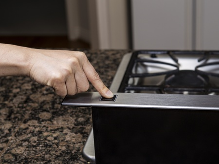 gas stove: Index finger pushing fan button on top of gas stove range  Stock Photo
