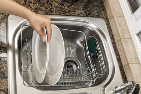Hand placing white dishes into drying pan in kitchen sink  Stock Photo - 13980311