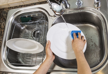 Hands washing dishes with running water from faucet in sink