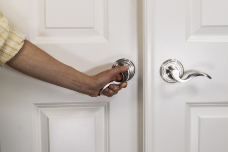 Hand pulling down chrome door handle on white panel door