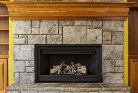stone fireplace: Natural Gas Insert Fireplace built with stone and wood  Stock Photo