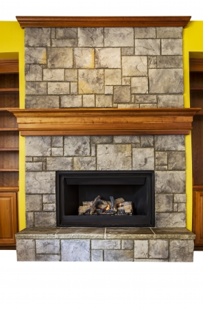 Full Vertical shot of gas insert fireplace with yellow accents walls and oak wooden shelves  photo