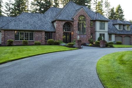 cedro: Casa grande y moderno con la hierba verde de peluche en el patio delantero y maderas en el fondo