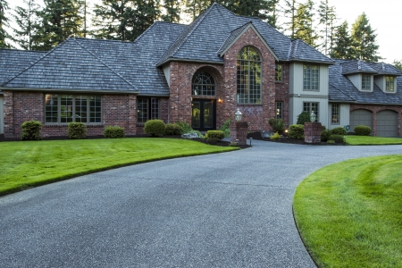 driveways: Modern large home with plush green grass in front yard and woods in background  Stock Photo