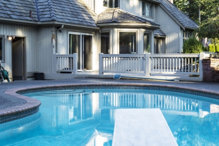 patio deck: Piscina riscaldata all'aperto con grande casa in background con alberi verdi