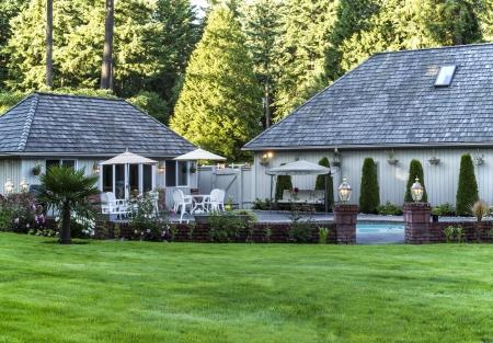 Grote achtertuin met pluche groene gras, bomen, een zwembad en huis op de achtergrond