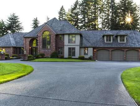 driveways: Driveway to large brick and cedar home with trees and sunlight in background