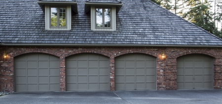 garage: Four car garage doors made of wood and brick with trees and sky in background