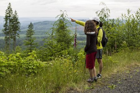 Mother and daughter hiking on mountain trail during summer  photo
