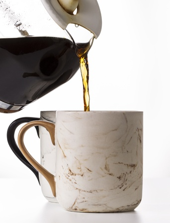Pouring fresh coffee into porcelain mug on white background Stock Photo - 14521610