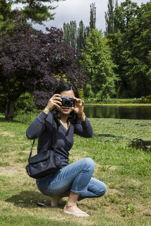 sandal tree: Mature Asian lady with small camera with lake, trees and sky in background