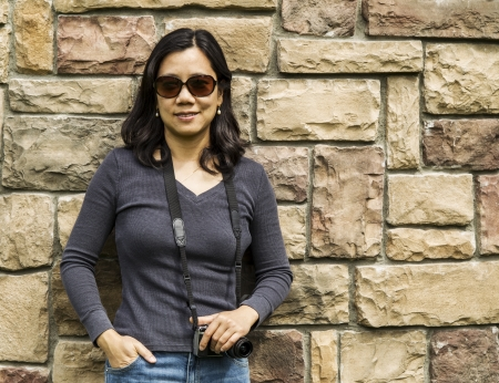 Mature Asian women holding camera with stone wall in background  photo