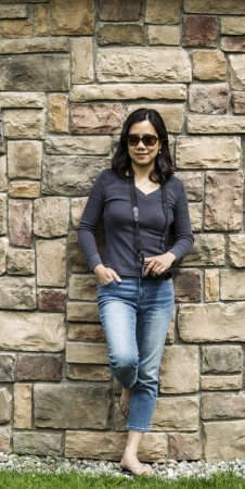 Mature Asian women holding camera with stone wall in background- full body shot photo
