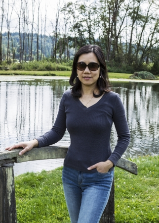 Mature Asian women standing on wooden bridge with lake and trees in background
