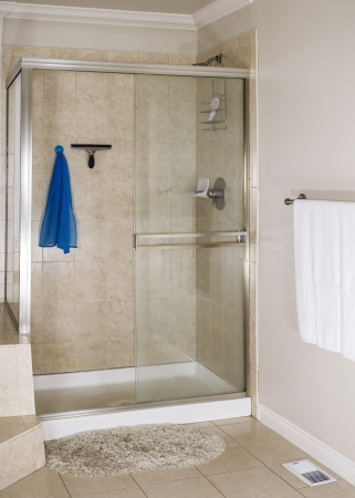 Clean master bathroom shower with scrub rag, squeegee and soap in dish  Stock Photo