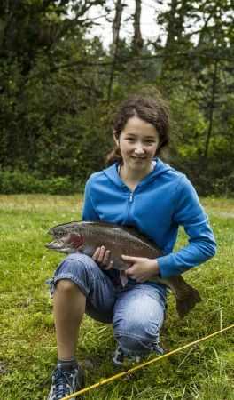 Young girl holding trophy rainbow trout with trees and sky in background  photo