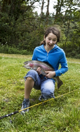 freshwater fish: Preteen girl expressing happiness after catching trophy trout with trees and sky in background  Stock Photo
