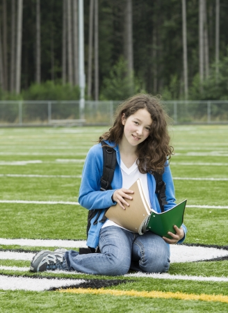 Young girl studying on soccer field with woods in background photo