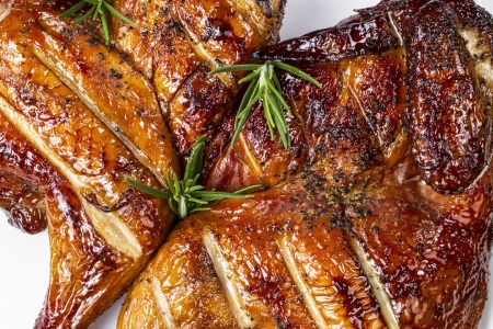 Fresh barbecued smoked half hen chicken with rosemary on top photo