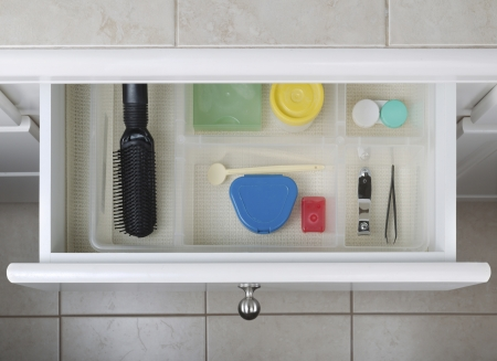 Open bathroom drawer with personal hygiene accessories displayed   photo